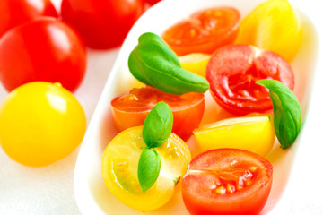 Red and yellow cherry tomatoes in plate on white tablecloth clos