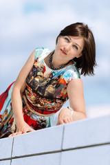 Model in dress posing on exterior set vertical