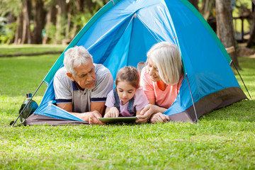 Grandparents With Granddaughter Using Digital Tablet At Campsite