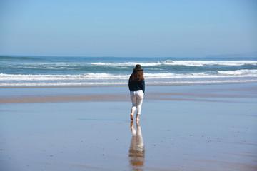 mujer caminando por la playa en primavera