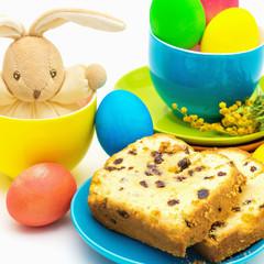 Пасхальный натюрморт с кроликом, разноцветными яйцами и куличом.