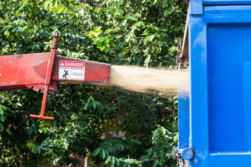 Wood chipper machine releasing the shredded woods into a truck