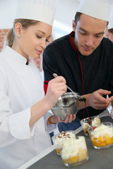 Chef with student in pastry making dessert