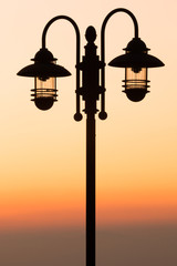 silhouette lamp on sunset background