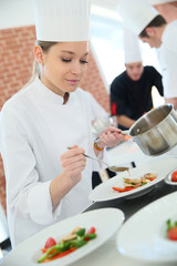 Young woman in cooking class pouring sauce on plate