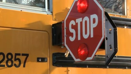 Two takes of the stop sign on a school bus swinging out to signal drivers to stop for school children.