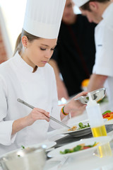 Girl in cooking training class preparing dish