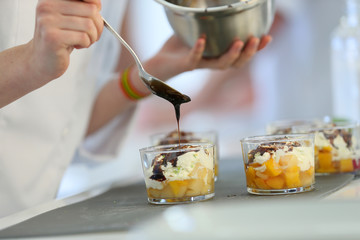 Closeup of chocolate being poured on dessert