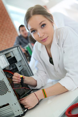 Student girl in technology fixing computer hard drive