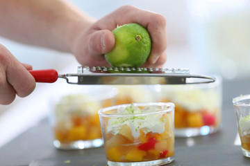 Cook rubbing lemon zest with grater over dessert