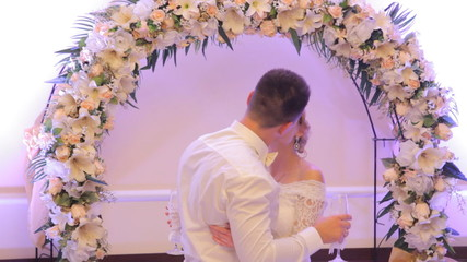 Bride and groom kissing in a restaurant while standing under