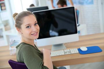 Portrait of student girl sitting in front of desktop