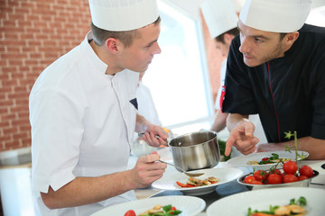 Chef with young cook in kitchen preparing dish
