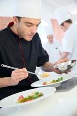 Chef in restaurant kitchen preparing dish