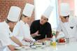 Chef training students in restaurant kitchen - 79638960