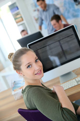 Portrait of student girl sitting in front of desktop