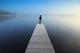 Man standing alone on a jetty, looking over a foggy lake.
