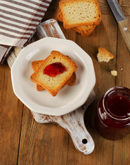Strawberry jam topping a slice of toast on  plate.