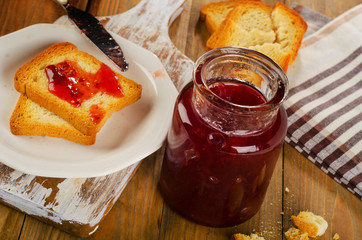 Strawberry jam topping a slice of toast on a plate.