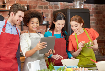 happy friends with tablet pc cooking in kitchen