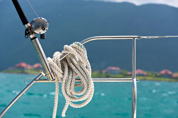 A rope tied around a lifeline and a fishing rod on a yacht