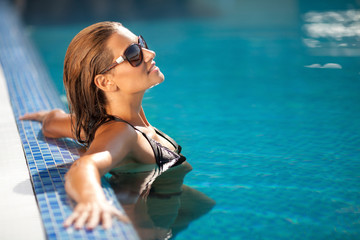 Beautiful woman in black bikini relaxing in the swimming pool