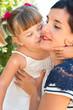 Little girl kissing her mum