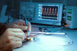 Tech tests electronic equipment in service facility - 79645375