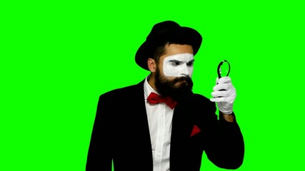 Man mime looks uses magnifier on green screen