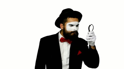 Man mime looks uses magnifier on white background