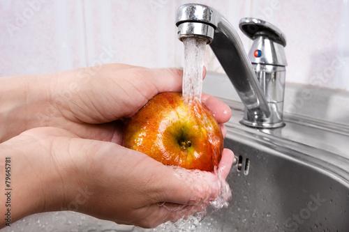 hands washing apple under water - 79645781