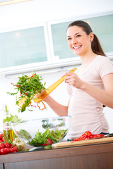 Young woman in the kitchen prepare salad XI