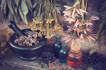 Vintage stylized photo of  healing herbs bunches, mortar and oil
