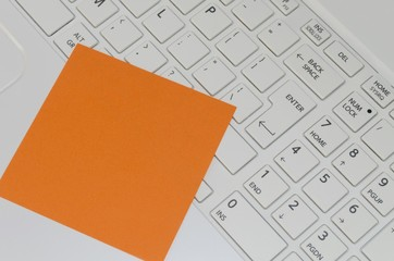 Orange reminder note on white computer keyboard