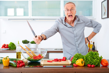 Aggressive mature man in the kitchen with knife