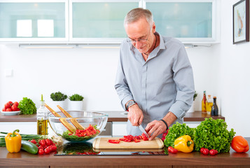 Mature man in the kitchen prepare salad XI
