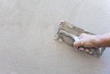 Plaster concrete worker at wall of house