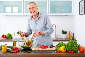 Mature man in the kitchen prepare salad VI