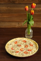 Red and yellow tulips and open cheese pie with chili on wooden b