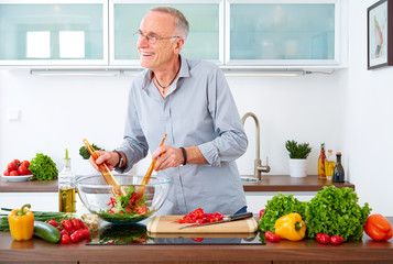 Mature man in the kitchen prepare salad VII