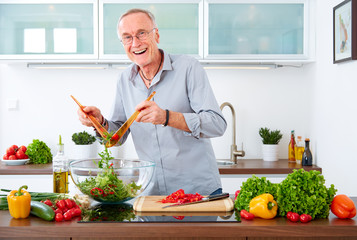 Mature man in the kitchen prepare salad VIII