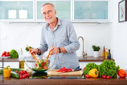 Mature man in the kitchen prepare salad VI - 79649918