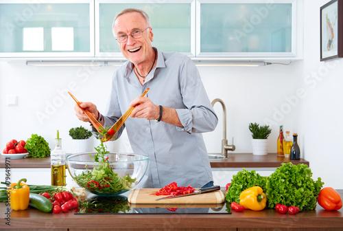 Mature man in the kitchen prepare salad VIII Poster