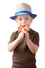 little boy licking lollipop in a hat
