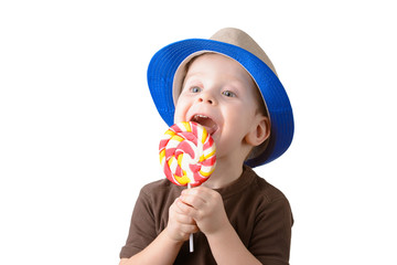 little boy licking lollipop in a hat closeup