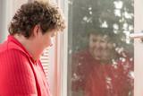 Geistig behinderte Frau sieht ihr Spiegelbild im Fenster