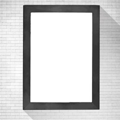 Black wooden frame with white copy space hanging on brick wall.