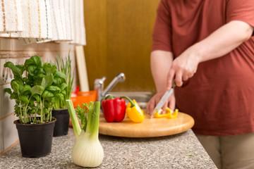 Beleibter Mann schneidet frisches Gemüse