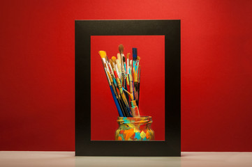 Arts painting brushes in frame with red background