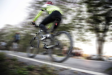Low angle view of cyclist riding mountain bike with speed effect